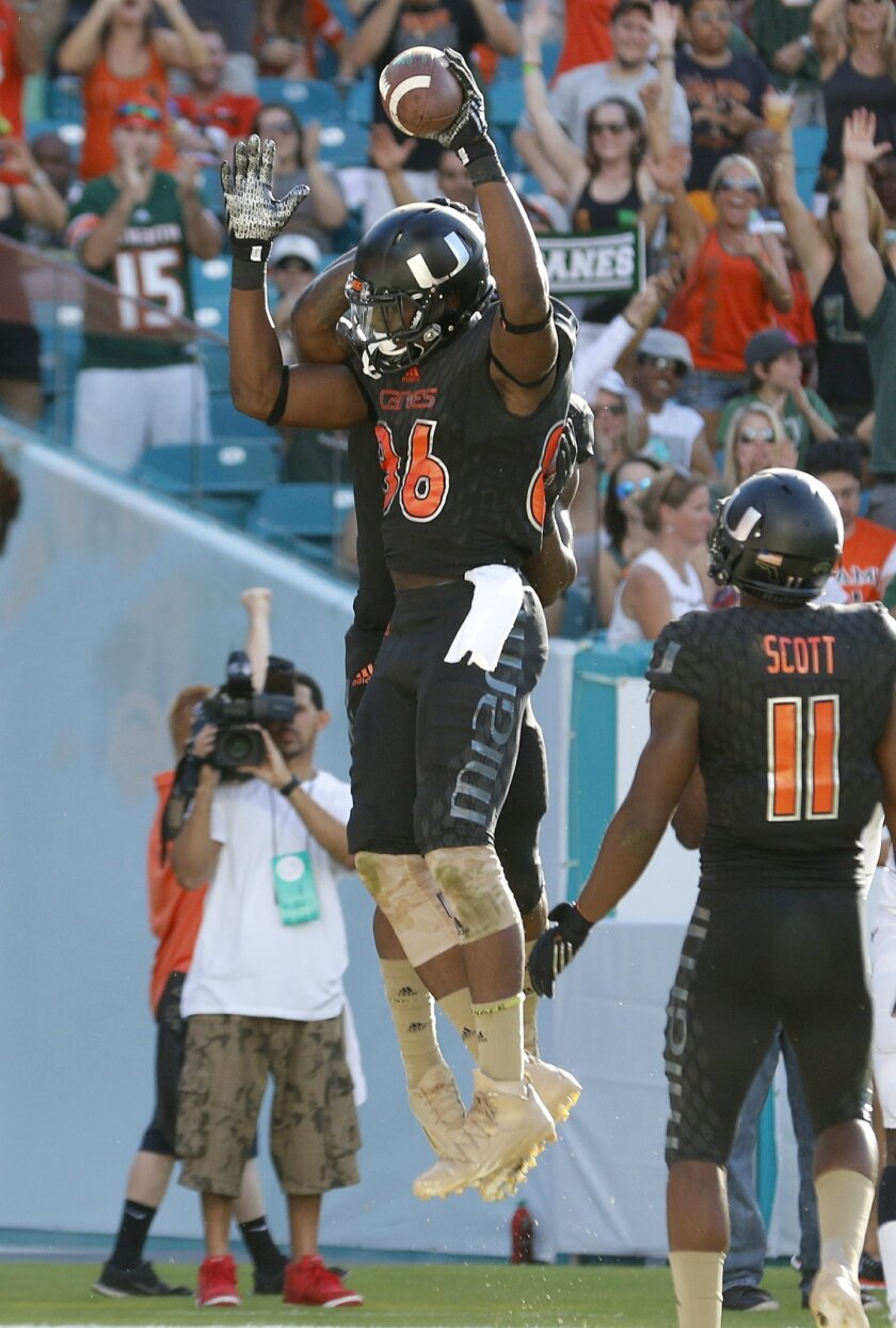 Miami tight end David Njoku (86) celebrates with teammates after his second quarter touchdown reception against Virginia in an NCAA college football game, Saturday, Nov. 7, 2015, in Miami Gardens, Fla. (AP Photo/Joe Skipper)