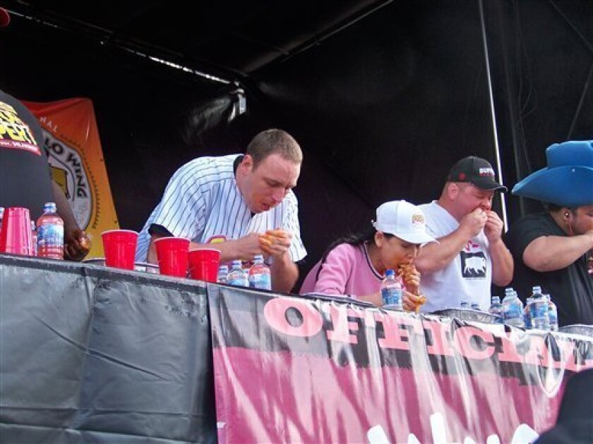 In this photo provided by National Buffalo Wing Festival, Joey Chestnut, left, competes with Sonya Thomas, center, at 2010 Wing Fest in Buffalo, N.Y., Sunday, Sept. 5, 2010. Thomas, The Black Widow of eating contests gobbled up nearly 181 chicken wings in 12 minutes, devouring the national championship record. (AP Photo/National Buffalo Wing Festival, Brian Kahle)