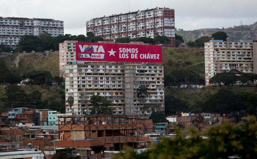 """In this Dec. 6, 2015 photo, the emblematic 23 De Enero apartment complex is covered with a banner that reads in Spanish """"Vote for PSUV, we're those of Chavez"""" during congressional elections in Caracas, Venezuela. The district patrolled by pro-government motorcycle gangs turned against the socialist party for the first time Sunday, part of a tide of voters who punished the government for the country's collapsing economy and handed the opposition a landslide victory in legislative elections. (AP Photo/Alejandro Cegarra)"""