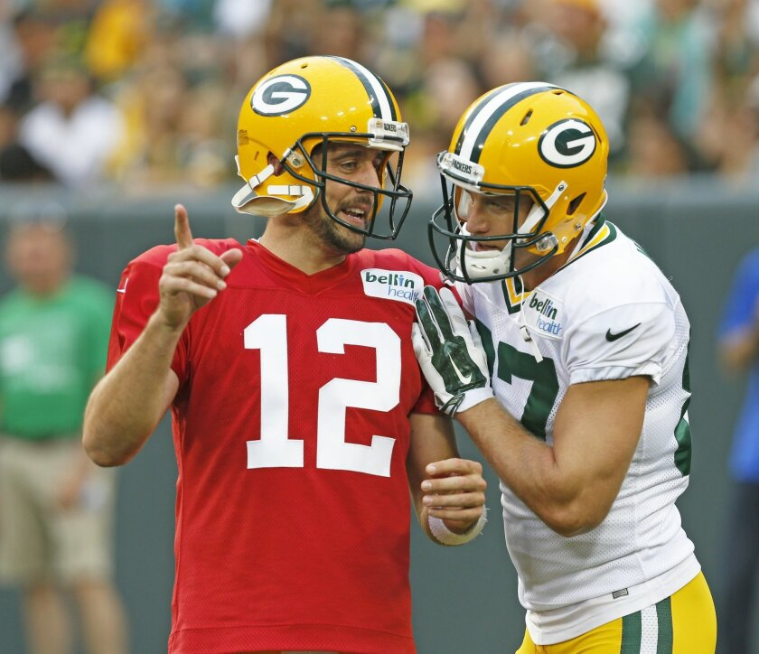 FILE - In this Aug. 8, 2015, file photo, Green Bay Packers' Aaron Rodgers, left, and Jordy Nelson talk during the Green Bay Packers Family Fun Night NFL football training camp practice in Green Bay, Wis. Few receivers are as important to their teams as Nelson is to Aaron Rodgers and Green Bay. Nelson injured his left knee in a preseason game against the Pittsburgh Steelers on Sunday, Aug. 23, 2015. (AP Photo/Mike Roemer, File)