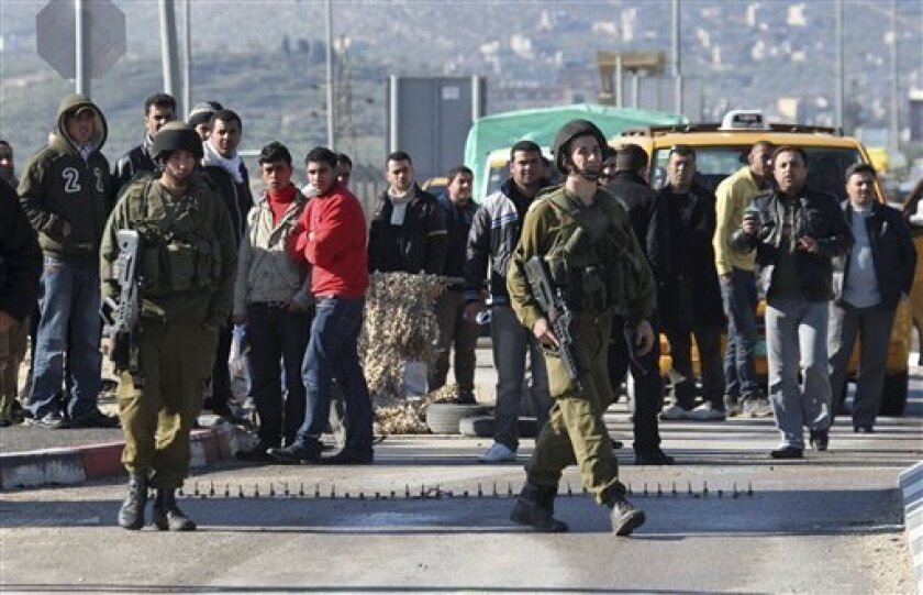 Israeli soldiers man Hawara checkpoint as Palestinians wait to cross, near the West Bank town of Nablus, after five people were killed in the nearby Jewish settlement of Itamar Saturday, March 12, 2011. A Palestinian infiltrated Itamar early Saturday and killed five people, the Israeli military said. Israeli media is reporting that the dead are all members of the same family with parents and three children aged 11, 3 and an infant, all reported to have been stabbed while they slept. (AP Photo/Nasser Ishtayeh)
