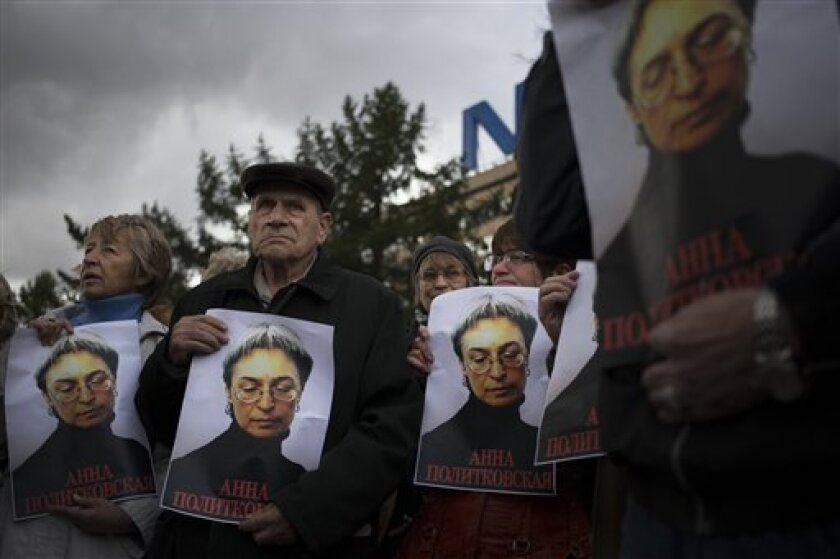 People rally, holding portraits of slain journalist Anna Politkovskaya, in downtown Moscow, Sunday, Oct. 7, 2012. About 200 people rallied Thursday on the 6th anniversary of the killing of Anna Politkovskaya, calling on the authorities to find and punish the killers of journalists and human rights