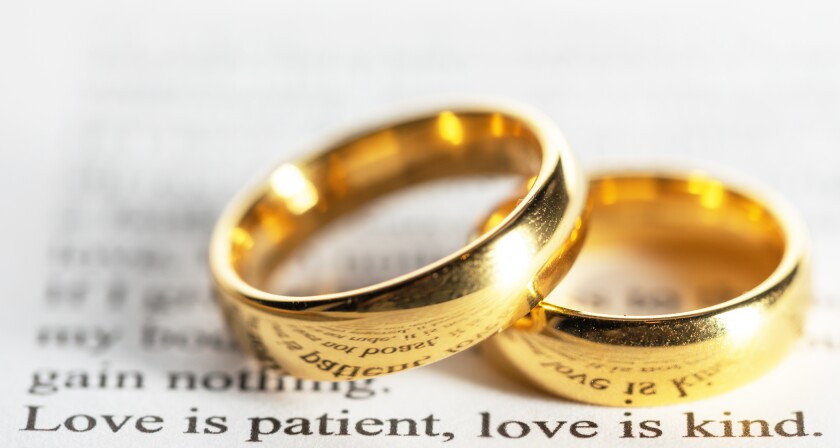 "Two golden wedding rings on Bible close up above ""Love is patient. Love is kind."""
