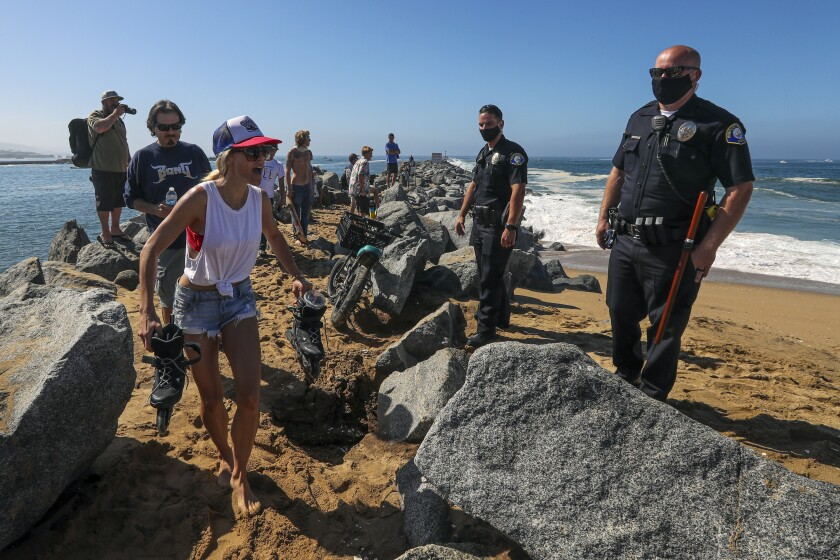 NEWPORT BEACH, CA - JULY 04: Newport Beach police enforces closure of beach along the Wedge in Newport Beach, a very popular and famed surf spot. (Irfan Khan / Los Angeles Times)
