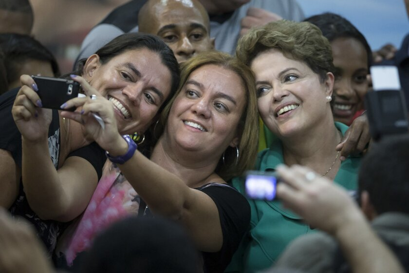 Brazil's President Dilma Rousseff, right, who is running for reelection with the Workers Party (PT), poses for selfie photos with supporters after a meeting with athletes as she campaigns in Rio de Janeiro, Brazil, Tuesday, Sept. 30, 2014. Brazil will hold general elections on Oct. 5. (AP Photo/Fel