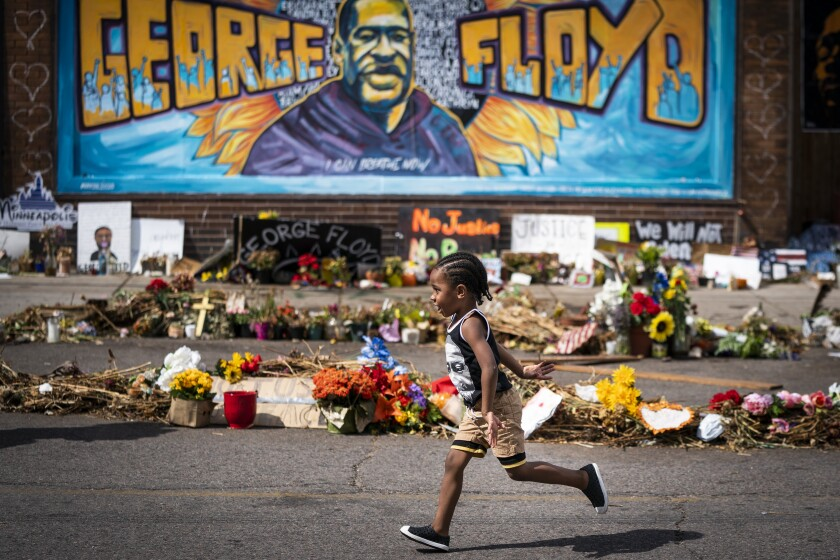 A small boy runs past a mural overlooking the George Floyd street memorial in Minneapolis