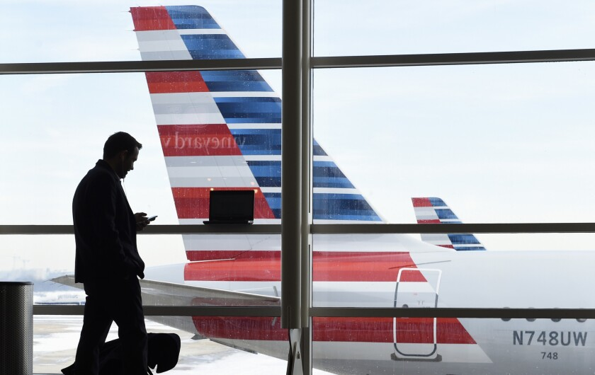 A traveler talks on the phone as American Airlines jets sit parked at Washington's Ronald Reagan National Airport in 2016.