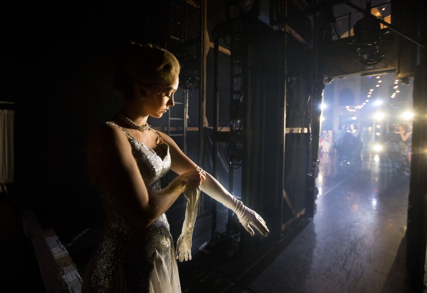 Ashley Shaw puts on long white gloves backstage before going out to play Cinderella.