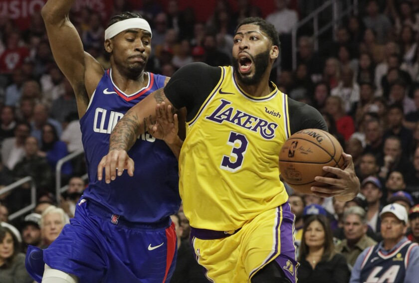 Lakers forward Anthony Davis (3) drives against Clippers forward Maurice Harless during the season opener