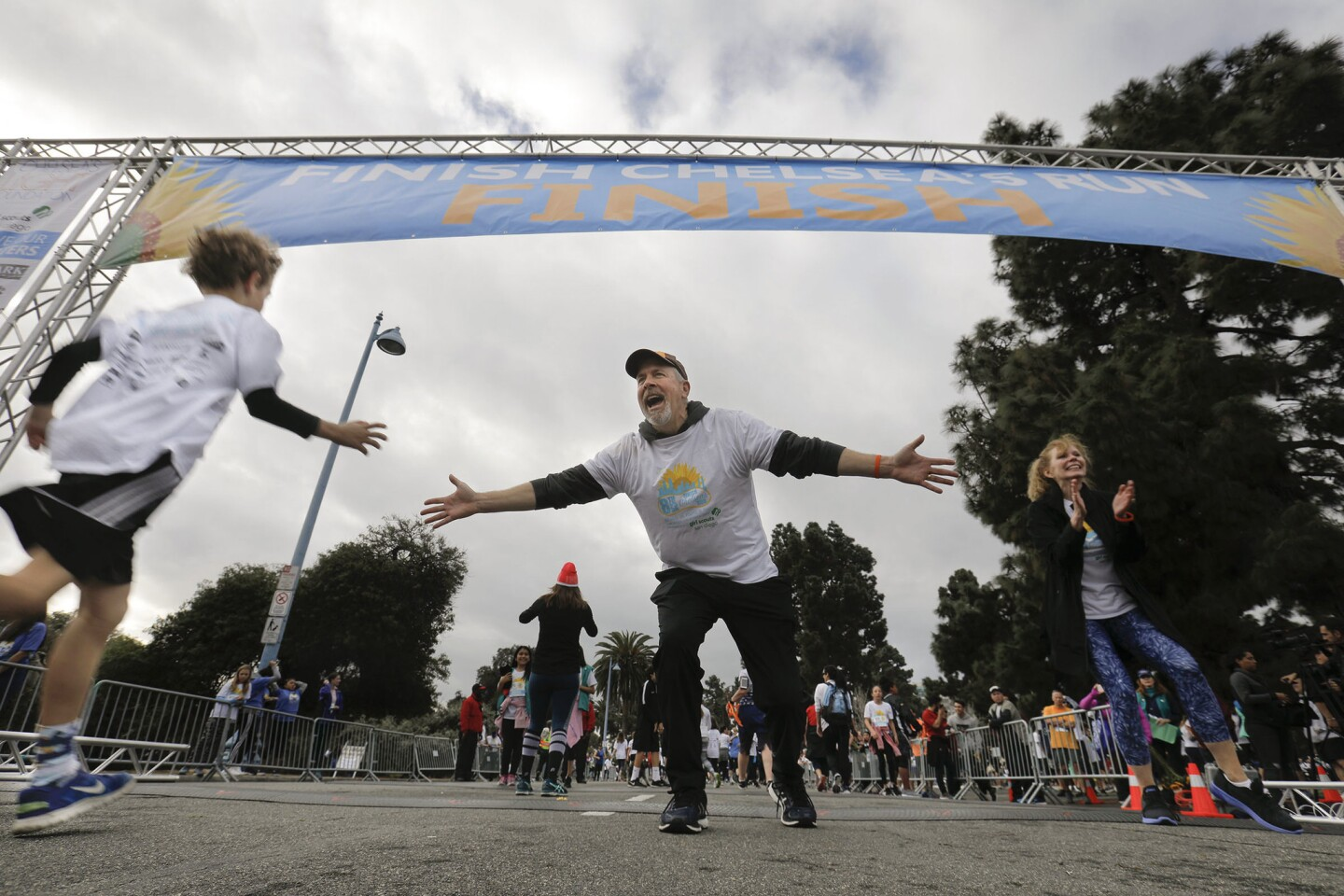 Brent King, center, and Kelly King, right, the parents of Chelsea King who was a 17-year-old Poway High student when she was killed by a sexual predator in 2010, greeted runners as they crossed the finish line in Balboa Park at the end of the 8th annual Finish Chelsea's Run 5K walk/run in memory of their daughter.