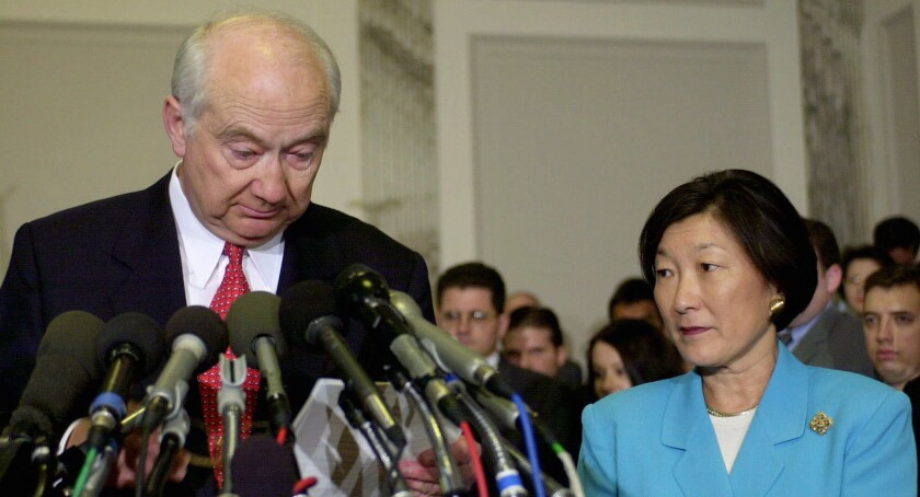 Phil Gramm, with wife Wendy at his side, announces his retirement from the Senate in the wake of the 2001 Enron collapse, which cost the couple a reported $600,000.