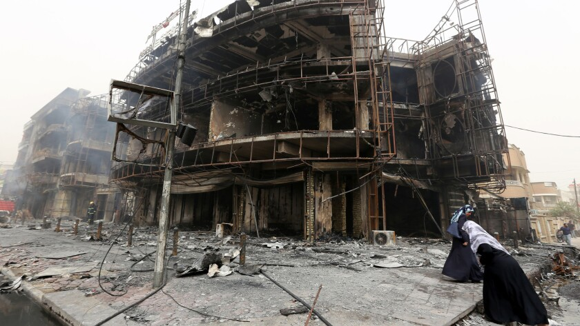 Iraqi women walk past a damaged building at the site of a suicide car bombing in Baghdad's central Karada district.