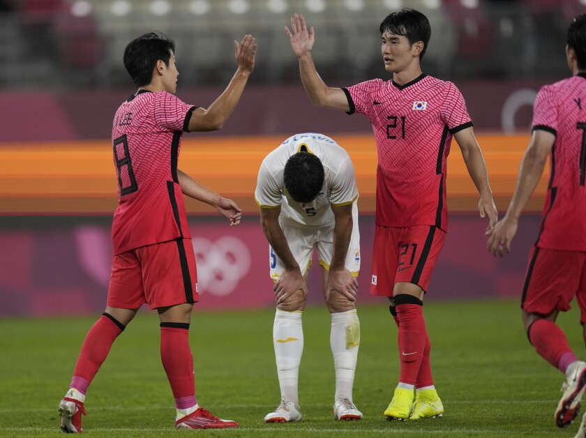 South Korea's Lee Kangin, left, celebrates with his teammate Kim Jingyu, right, after scoring his side's fourth goal as Tudor Baluta of Romania, center, looks down during a men's soccer match at the 2020 Summer Olympics, Sunday, July 25, 2021, in Kashima, Japan. (AP Photo/Fernando Vergara)