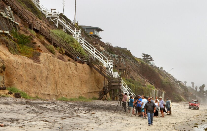 View of a large seawall below homes above at the 1500 block of Neptune Ave. At lower right is a Surfrider Foundation press conference where they spoke against the walls.