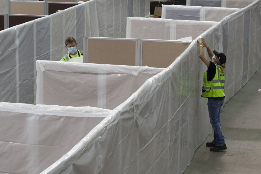 Sheeting is placed on partitions installed between beds as work is performed to turn the Sleep Train Arena into a hospital
