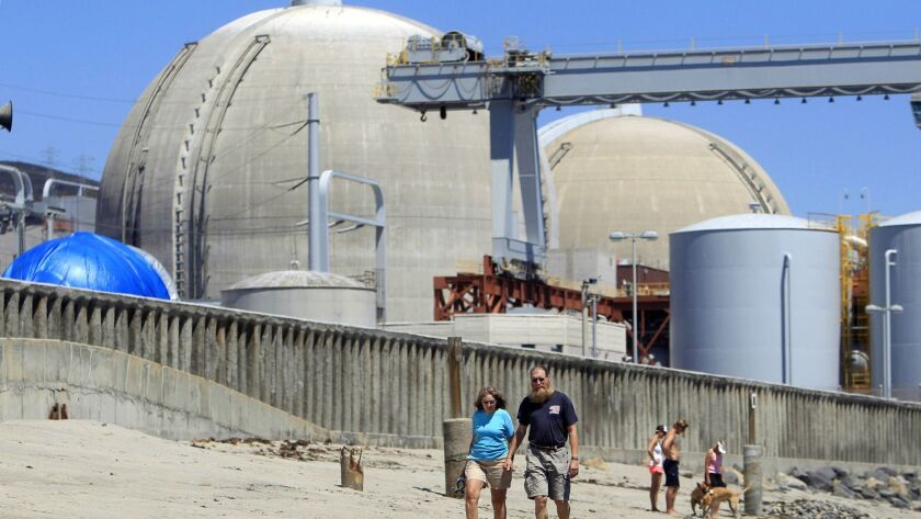 People walk on the sand near the shuttered San Onofre nuclear power plant near San Clemente in 2011.