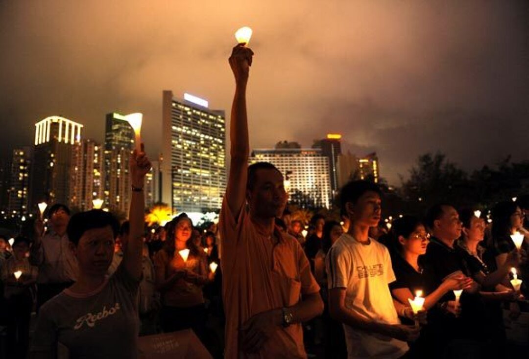 A man holds a candle as tens of thousands people stage a candlelight vigil at Hong Kong's Victoria Park