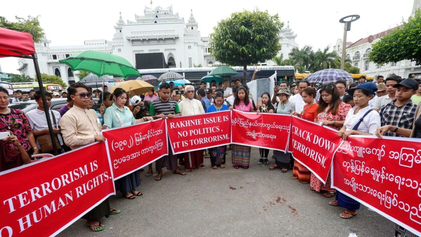 Myanmar nationalists hold posters during a rally in Yangon, Myanmar, on Aug. 30 protesting the repor