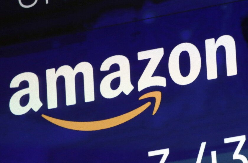 FILE - In this July 27, 2018 file photo, the logo for Amazon is displayed on a screen at the Nasdaq MarketSite in New York. Amazon must decide soon if it will protest the Pentagon's awarding of a $10 billion cloud computing contract to rival Microsoft on Oct. 25, 2019, with one possible grievance being the unusual attention given to the project by President Donald Trump. Amazon was long thought to be the front-runner in the competition for the huge military contract. (AP Photo/Richard Drew, File)