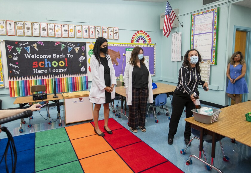 Women in masks stand in a classroom.
