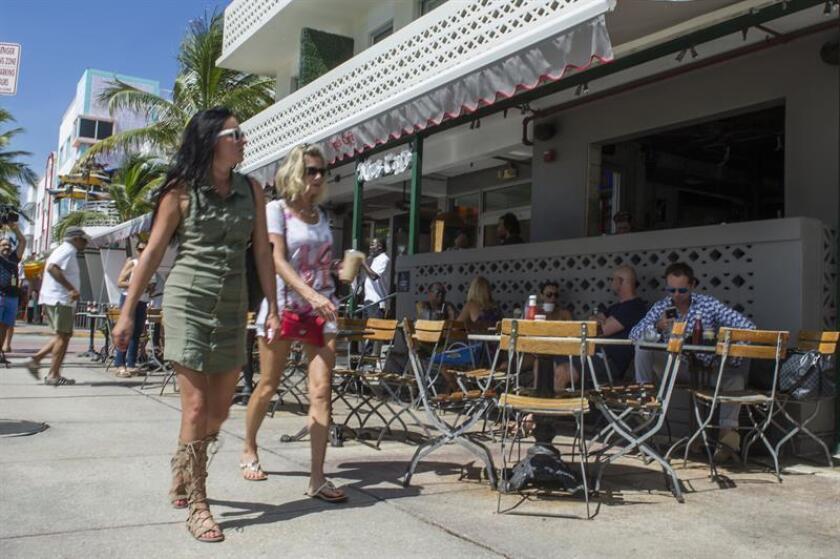 Unas turistas caminan frente el famoso Ocean Drive en Miami Beach, Florida. EFE/Archivo