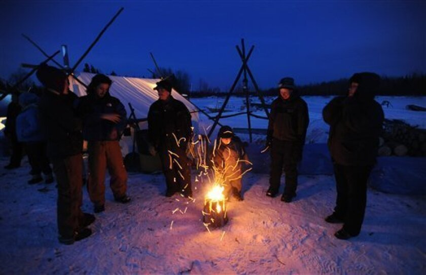 Four-year-old Kayden Alexie pokes a fire with a stick as people gather in the village of Nikolai, Alaska, to watch and help with dog teams pulling into the checkpoint during the Iditarod Trail Sled Dog Race, Tuesday, March 5, 2013. (AP Photo/Anchorage Daily News, Bill Roth)