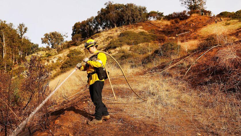 MALIBU, CA - JANUARY 29, 2018: Los Angeles County Firefighter Jake Whiteaker douses hot spots on a s