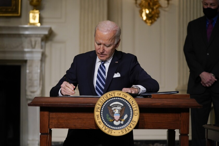President Joe Biden signs an executive order in the White House