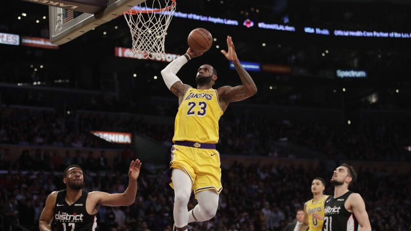 Lakers' LeBron James, center, goes up for a dunk as Washington Wizards' Jabari Parker, bottom left, and Tomas Satoransky look on during the first half on Tuesday at Staples Center.