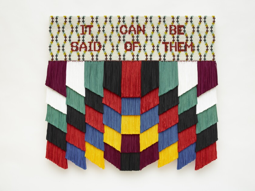 """A multimedia art work features fringe in a geometric pattern topped by the phrase """"It Can Be Said of Them"""" in beads."""