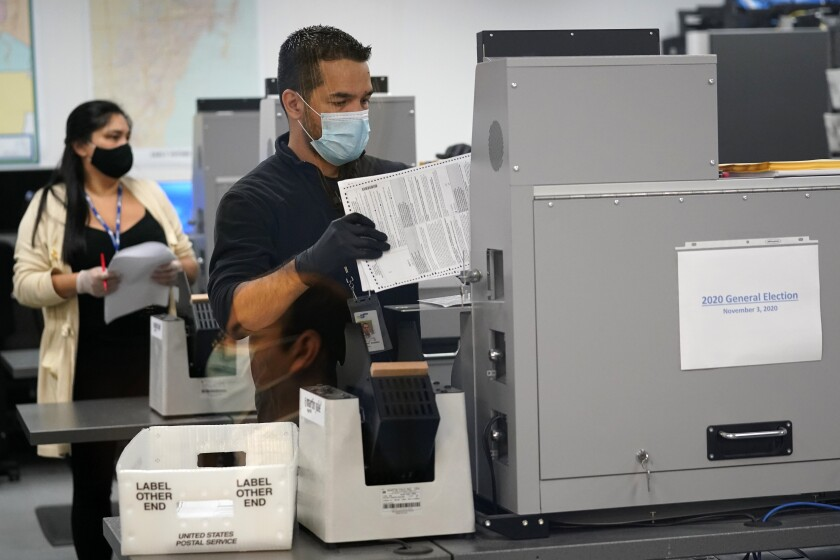 An election worker loads ballots into a scanning machine on Monday in Doral, Fla.