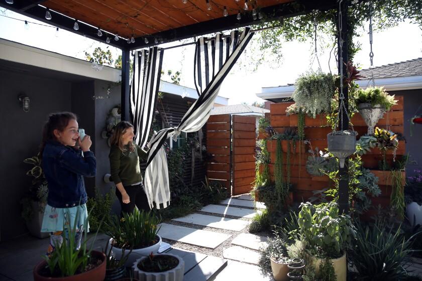 Allison Glatstein helps daughter Nili take a photograph of the vertical garden.