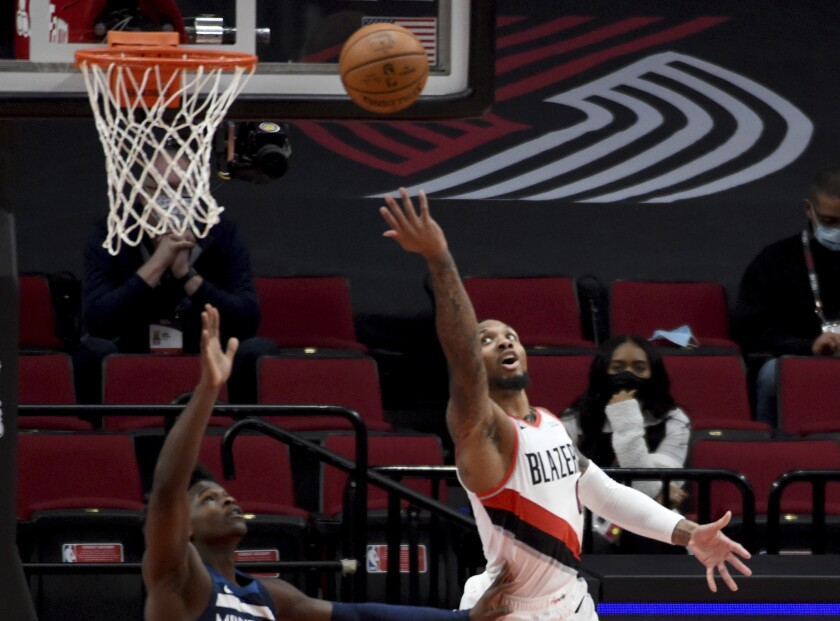 Portland Trail Blazers guard Damian Lillard, right, lays the ball in over Minnesota Timberwolves guard Anthony Edwards, left, during the first half of an NBA basketball game in Portland, Ore., Thursday, Jan. 7, 2021. (AP Photo/Steve Dykes)