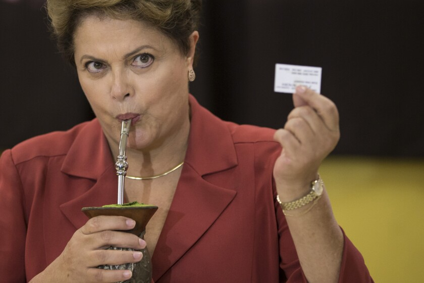Brazilian President Dilma Rousseff, sipping mate herbal tea, shows her electronic voting receipt Sunday.