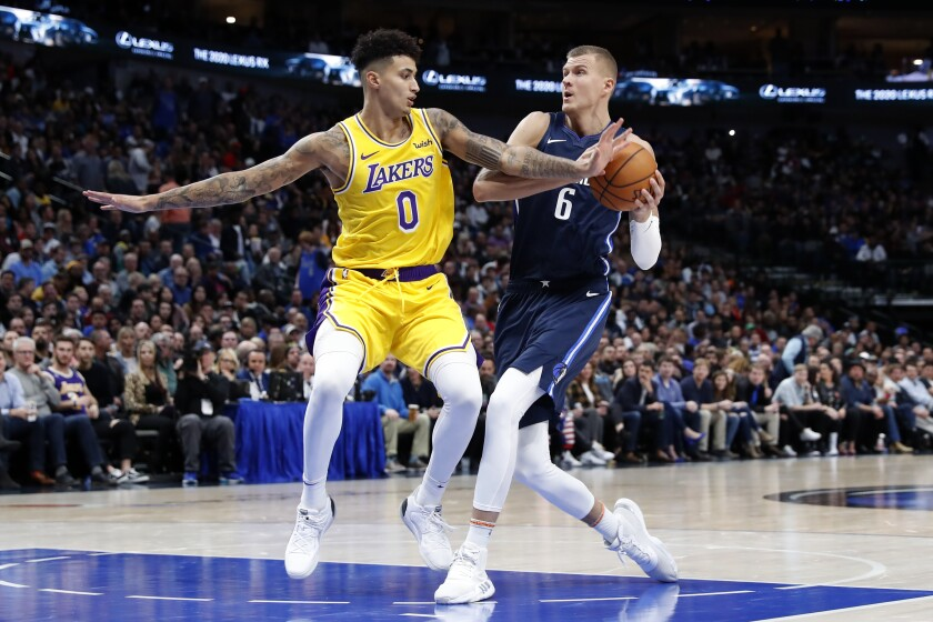 Lakers forward Kyle Kuzma defends Mavericks forward Kristaps Porzingis (6) as he drives to the basket during the second half of a game Nov. 1.
