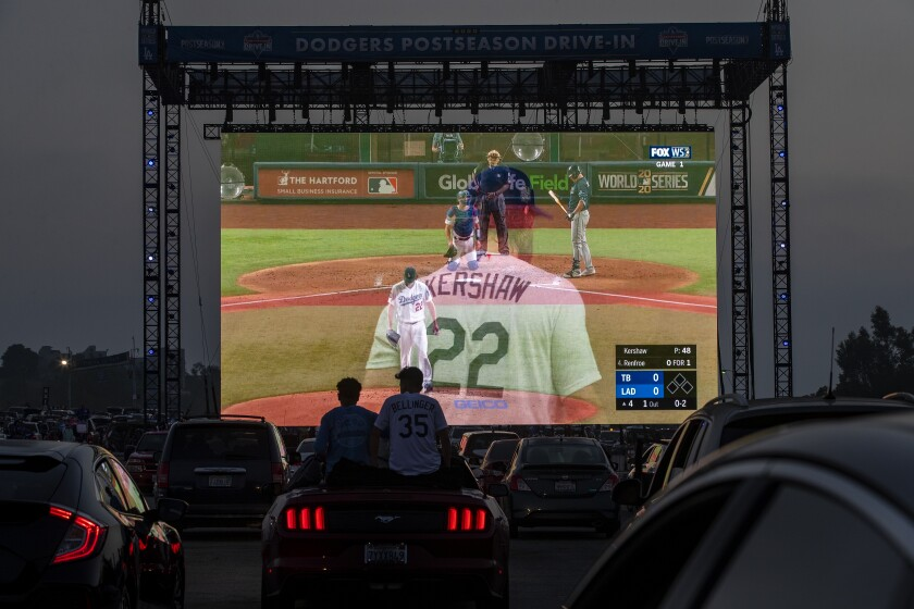 Fans sit on the back seat of their car to watch Game 1 of the World Series during a drive-in viewing at Dodger Stadium.