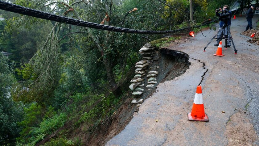 A landslide on Aitken Avenue from an overnight storm threatens homes Friday in Oakland.