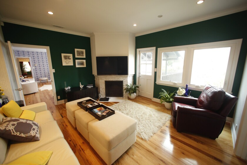 """Thurmond's den features hunter green walls, patterned wallpaper and a sofa. """"I wanted it to be relax"""