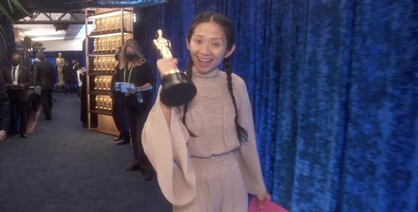 "Chloe Zhao holding one of her Oscars for ""Nomadland"" backstage."