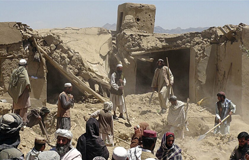 Afghan villagers gather at a house destroyed in an apparent NATO raid in Logar province, south of Kabul.