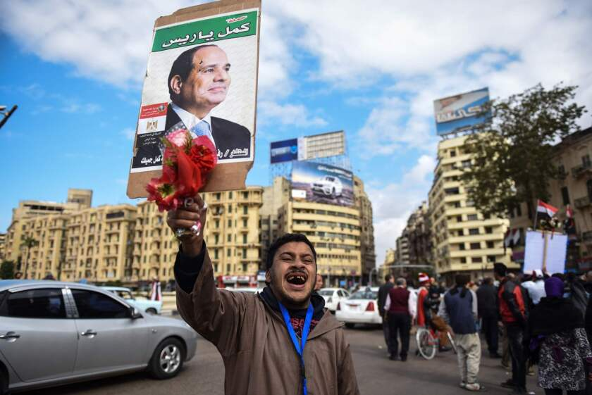 A pro-government Egyptian man holds up a portrait of President Abdel Fattah Sisi in Cairo's landmark Tahrir Square on Monday.