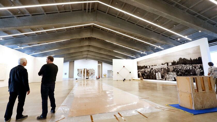 Maurice Marciano, left, photographed on the third floor of during the installation of the opening ex