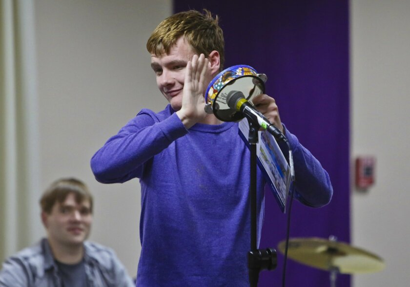 "Reid Moriarty, a 20-year-old man with autism from Solana Beach, leads a group of other autistic and Down syndrome youth on Wednesday night in Music Therapy of San Diego's weekly Banding Together program. Reid is releasing his debut CD for children, ""Purple Party,"" on Saturday. Photo by Don Boomer"