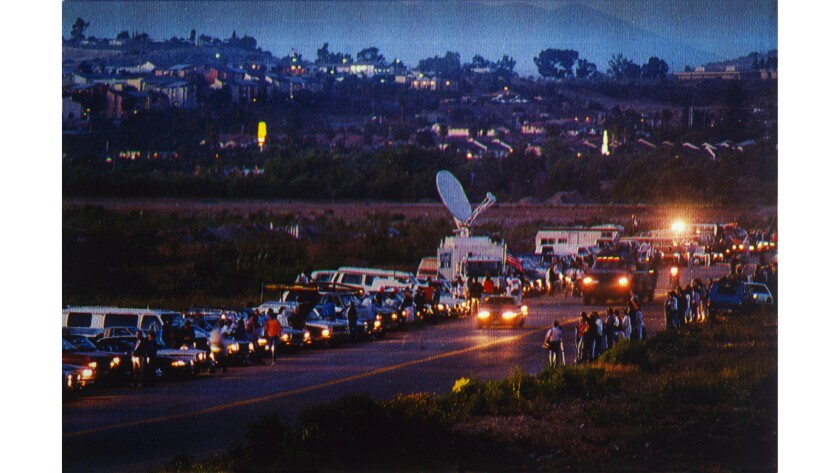 May 25, 1990: Supporters of the Light Up the Border movement shine headlights across a San Diego road, past a line of counterprotesters, to illuminate an area where immigrants enter the United States.