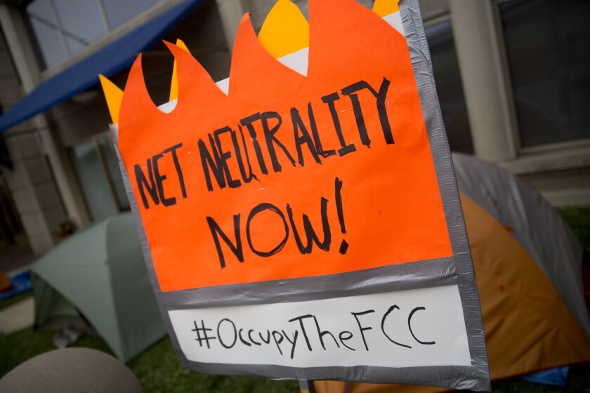The battle begins: An advocate of net neutrality grabs a prime spot at FCC headquarters ahead of Thursday's vote.
