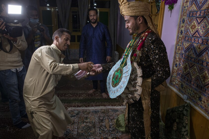 A Kashmiri man sprays sanitizer on the hand of Haseeb Mushtaq, a Kashmiri groom as he arrives at brides home during his wedding ceremony on the outskirts of Srinagar, Indian controlled Kashmir, Monday, Sept. 14, 2020. The coronavirus pandemic has changed the way people celebrate weddings in Kashmir. The traditional week-long feasting , elaborate rituals and huge gatherings have given way to muted ceremonies with a limited number of close relatives attending. With restrictions in place and many weddings cancelled, the traditional wedding chefs have little or no work. The virus has drastically impacted the life and businesses in the region. (AP Photo/ Dar Yasin)
