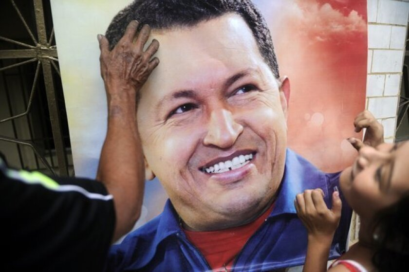 A poster of Hugo Chavez is hung as Venezuela mourns its former president. Even after Chavez's death, experts predict that gasoline will still be heavily subsidized by the government.