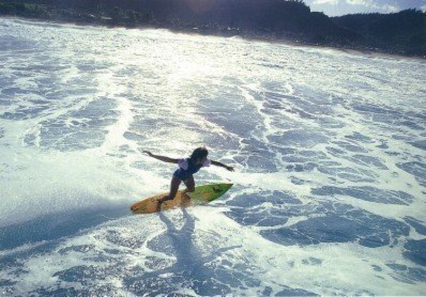 WindanSea Surf Club's Debbie Beacham catches a wave at Sunset Beach on Oahu's North Shore in the early '80s. Courtesy