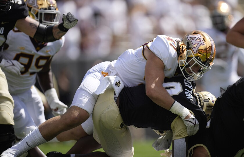 Minnesota linebacker Jack Gibbens, top, wraps up Colorado running back Ashaad Clayton after a short gain in the second half of an NCAA college football game Saturday, Sept. 18, 2021, in Boulder, Colo. Minnesota won 30-0. (AP Photo/David Zalubowski)