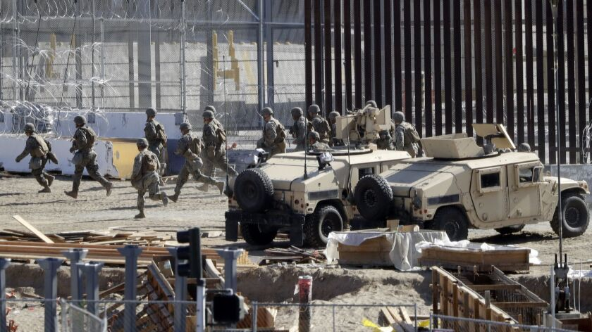Officials run in a staging area in the San Ysidro port of entry at the U.S.-Mexican border on Sunday.
